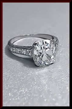 Classic sophistication resonates in this art deco 1930's platinum engagement ring. The stunning center old cushion cut diamond weighs approx.