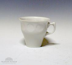 Kaffekopp av porselen med hvit glasur. Sirkler i relieff øverst på koppen. Prøve til nytt servise. Ikke satt i produksjon. Design: Konrad Galaaen.