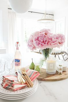 Flowers, whether in a large or simple arrangement, can change the dynamic of an entire room. These large pink peonies add a fun, fresh vibe to this dining room set-up!