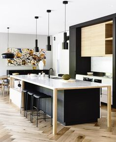 Love the combination of exposed wood, black cabinets and white worktop. It all works together to create a fluid, contemporary kitchen.