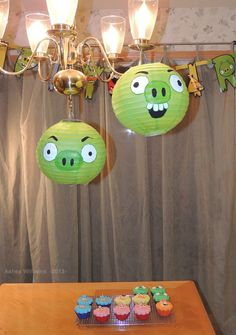 Homemade Angry Bird Decorations & Cupcakes. These Pigs are easy and cheap to make. They are just green paper lanterns, that I just free-handed some pig faces on using white & black acrylic paint. These could be used for a birthday party game or decorations.