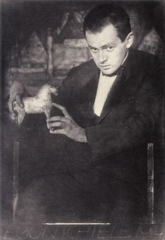 """Egon Schiele with his carved wooden horse. In the background, the painting:""""Row of Houses"""". Photograph, presumably by Anton Josef Trcka. 1914. Albertina Museum, Vienna."""