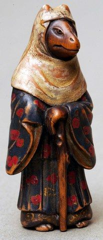 This netsuke shows a fox wearing a dress and a cloak. According to ancient Japanese beliefs, the fox is a magical creature that is able to transform itself into a human figure. Bequeathed by Miss Edith Taylor in 1959