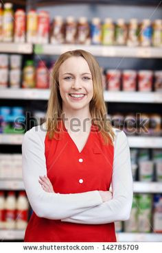 Portrait of beautiful saleswoman with arms crossed standing in grocery store