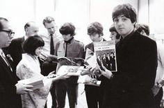 The Beatles and their producer George Martin (wearing a necktie, at back ) look through copies of Music Life.