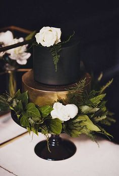 Black and gold cake, black stand, greenery, love. | Dark Wedding Cakes | Wedding Ideas | Brides.com