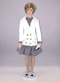 This Franklin Mint Diana doll is wearing a custom replica of a Catherine Walker dress with puff-ball skirt & white jacket that Diana wore as she attended the Cannes film festival on May 15, 1987 in Cannes France.