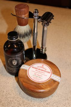 """The Village Cigar Company & Barbershop: If you want to keep your guy looking sauve even after he's left the shop, consider the """"Shaving Kit"""" (pictured) which includes a Merkur, Solingen razor, Marke Golddachs, Dachshaar badger brush, Dr. Harris & Co. Ltd stainless steel silver stand, shaving bowl and soap, Marlborough Mahogany bowl and Timeless Fragrance of Noble Character soap, and after shave by Crown Shaving Co. After Shave Tonic and all for under $250."""