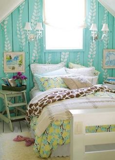 The leaves painted on turquoise wallare a fun way to update old wood paneling.  This little bedroom looks like an open space at the top of some attic stairs.