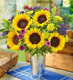 Brighten your day with this elegant sunflower arrangement kept in the rustic French flower pail.