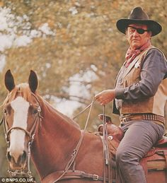 "John Wayne, arguably Hollywood's most loved Wild West hero, rode many trusty steeds during his long, successful career on the silver screen. Seen here as Rooster Cogburn in ""True Grit"" (1969) Wayne was aboard a horse called Dollor, who stayed with him through subsequent movies ""The Undefeated"", ""Rio Lobo"", ""Chisum"" and ""The Shootist""."