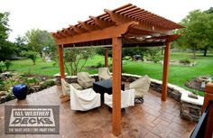 Cedar Pergola with Shades over Stamped Concrete Patio with Stone Walls and Columns and EverGrain Deck in Overland Park, KS