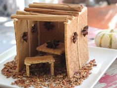 A sukkah is a temporary hut, or booth, built especially for the week-long Jewish harvest festival of Sukkot. Our sukkahs were constructed with cinnamon graham crackers, but your favorite gingerbread recipe would work just as well.  It is all held together with good old fashioned cookie-cement… aka Royal Icing.