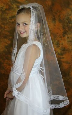 """$52 First Communion Veil Mantilla Style in Imitation Chantilly Lace From front to back (top of head to end of the veil), the length is 32"""". From side to side (shoulder to shoulder), the measurement is 52""""W. Floral border measures about 1 1/4""""W. Made of imitation Chantilly lace material. 100% cotton. Complete with a built in comb to secure. Please hand wash this veil to preserve it"""