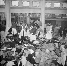 Sorteren van kleding voor slachtoffers van watersnoodramp in Rivièrahal, Rotterdam