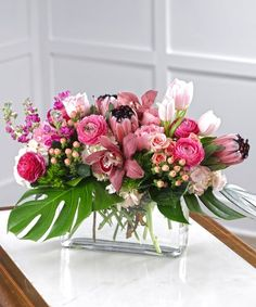 Pink Treasure Bouquet features pink garden roses and tea roses, stock, ranunculus, exotic orchids and feather pink protea. Hand-designed and delivered by Carithers Flowers in Atlanta.