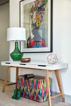 comment decorer un couloir en style ethnique africain, table avec des pieds en bois clair et plan blanc, lampadaire avec base en vert bouteille et abat jour blanc, malle de rangement en couleurs vives, tableau avec femme africaine en tonalités chaudes, parquet en bois clair