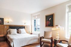 Paris Penthouse Vacation Rental // Sleek neutral-tone bedroom with wooden headboard and portrait painting.