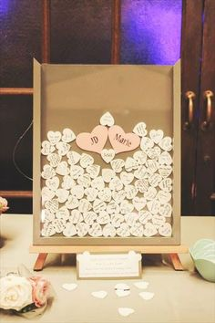 ave each guest sign a small wooden heart and drop it in a shadow box frame / http://www.deerpearlflowers.com/creative-wedding-guest-book-ideas/