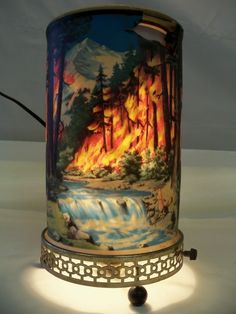 Vintage 1955 Econolite Motion Lamp Forest Fire Scene.  I was fascinated as a kid by one of these my Grandma had...  She passed it down to my Mom, and now I have it and LOVE it...  The heat of the lightbulb makes a (paper accordion style spindle) gently spin and makes the flames look alive and the water like it's rushing...