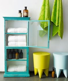 This vintage storage cabinet in vibrant turquoise pairs well with stools in invigorating hues of lemon and baby blue.