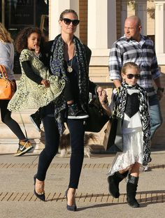 (Heidi Klum) That's right, looking hot, adorable kids with one on hip, holding hands, oversized bag, and shades...all while rocking the heels!