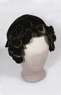 Flapper velvet skull cap, late 1920s. By the late 1920s, the bell shaped cloche was pared down even more to become a skull cap. The look of streamlined modernism, seen in all areas of design, seems fresh and relevant today. This essential flapper accessory is fashioned from black silk velvet and is lined with black felt. The hard-edge skull shape is softened with bouquets of black velvet petals that frame the face. Skull caps are perfect for bad hair days—just tuck your hair up inside the…