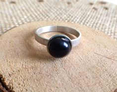 This beautiful and dainty ring exhibits a black 7.5 mm AAA grade freshwater pearl; it rests in a sterling silver cup, and is soldered to a
