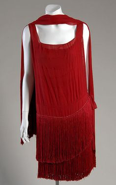 "Evening Gown, Coco Chanel (1883-1971), Paris, France: ca. 1925, silk chiffon with silk fringe.    ""This garment is one of the best examples of flapper-style dress in the museum's collection. The flat silhouettes, use of fringe, and sparkling embroidery are common features of the era."""