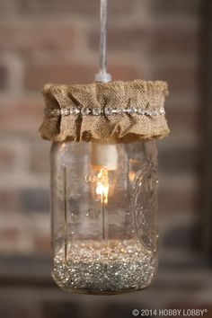 Hang some happy with help from our pendant light kits! There's no drilling, no wiring, no tinkering—you just screw them into place! For this DIY design, we used glass glitter and burlap trim. cute for kitchen w/out burlap Mason Jar Lighting, Mason Jar Lamp, Christmas Mason Jars, Christmas Lights, Jar Lights, Bottles And Jars, Mason Jar Crafts, My New Room, Diy Design
