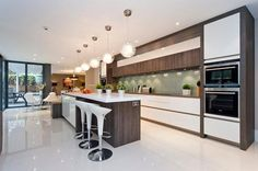 Modern white kitchen with reversed island design. Island is wood with white counter compared to main kitchen design of white with wood counter and trim. Open Plan Kitchen, New Kitchen, Kitchen Dining, Kitchen Decor, Kitchen White, Kitchen Modern, Luxury Kitchens, Cool Kitchens, Kitchen Handles