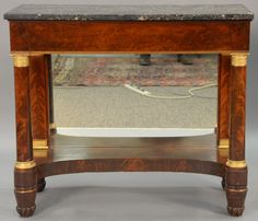 Classical mahogany pier table having grey marble top on base with gilt bronze mounted columns, mirror back with carved and turned feet, circa 1840. Realized Price $3,000.00