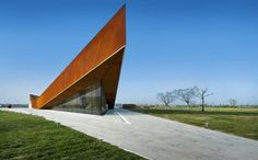 A band of Corten steel cladding surrounds the triangular building, pitching upwards at each corner to cantilever over triangular windows.