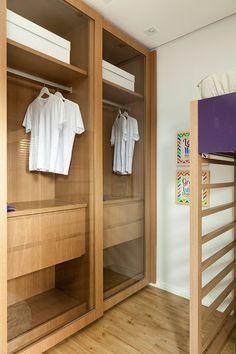 Decoração de apartamento pequeno e charmoso com ambientes integrados com ripas de madeira. Armário de madeira com portas de correr de vidro.