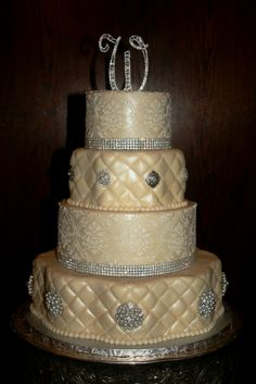 This wedding was held at Maggiano's in Atlanta, and was the centerpiece of the room.  The cake was alternating scallop and round tiers, adorned with jewels. #blissmcdonough #blisscakes #jeweledweddingcake
