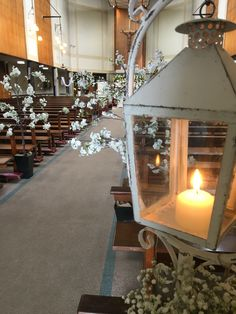 Posy Barn lanterns and trees line the church aisle