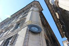 A clock sits on the side of a building in #PiazzaVenezia