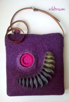 Borsa in feltro, lana bergshaf tinta e cardata, con decoro tridimensionale in colori contrastanti. La tracolla, in cuoio scuro, è cucita a mano con filo in tinta