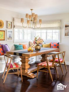 This colorful breakfast nook decorated with a wooden table, colorful pillows and a rustic chandelier was featured in HGTV Magazine. Take the full kitchen tour on HGTV.com.