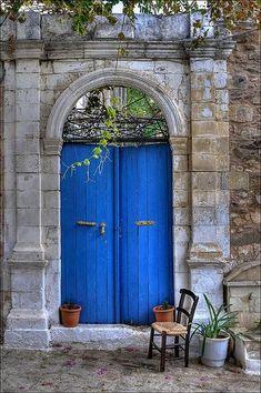 Porta de uma casa grega. O uso de pedra, os arco, a cor azul tão apreciada pelos gregos, tudo colabora para uma beleza simples.