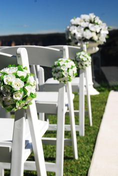 White folding padded chairs with white silk hanging balls, white carpet and urns and pedestals with silk floral arrangement Wedding Pews, Wedding Canopy, Wedding Ceremony Flowers, Wedding Ceremony Decorations, Wedding Chairs, Wedding Ceremonies, Silk Flowers, White Flowers, Types Of Wedding Cakes