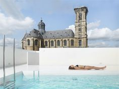 Belgian design studio dmvA architecten have given this old school house in the town of Grimbergen a stark minimal rooftop terrace featuring a bright turquoise swimming pool, which creates a beautiful contrast with the adjacent Baroque basilica. Swimming Pool Architecture, Old School House, Building A Pool, School Building, Swimming Pool Designs, Rooftop Terrace, World's Most Beautiful, Garden Pool, Cool Pools
