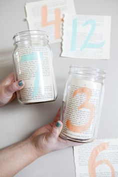 Simple DIY // Rip out pages from an old book, paint table numbers on the pages and put them into mason jars for your wedding table numbers... click to learn more!