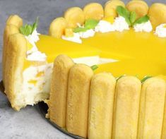 This photo shows serving a gorgeous piece of charlotte-style no bake mango cheesecake from a springform pan with contrasting yellow and white colors, so delicious and festive!