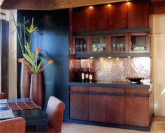 Hammered copper backsplash is complimented with brownish orange cabinets, vases and chairs.