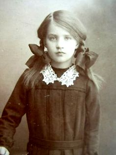 Antique photo of girl with pig-tails, big bows, white lace collar & dark dress