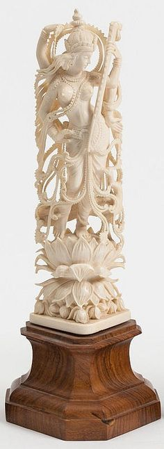 An Indian carved ivory figure: Sarswati standing on a lotus flower, mounted on a polished wood base, 27cm. high.