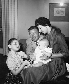 """Photograph caption dated May 17, 1956 reads, """"James Mason (here) has three very good reasons why he should keep on working. They are of course wife Pamela, Portland (left) and baby Alexander."""""""