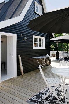 Ein schwarzes modernes Blockbohlenhaus mit der Terrasse. Lesen Sie mehr auf https://www.pineca.de/