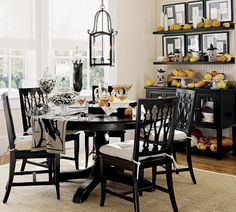 Dining Room Decorating Tips - this compact space uses striking black furniture as the backbone to the look, repeated in the lighting fixture, black & white photo ledges, table runner, etc.